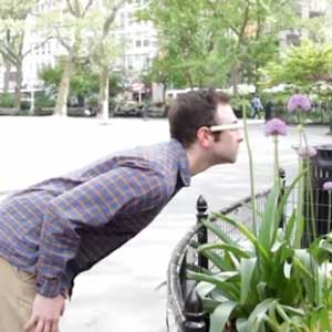 Person wearing Google Glass bending over to take pictures of flowers