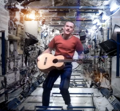 Chris Hadfield floating with his guitar in the ISS