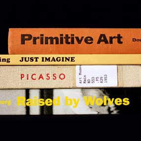 """Book spines: """"Primitive Art"""" """"Just Imagine"""" """"Picasso"""" """"Raised by Wolves"""""""
