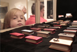 Child looking at miniature books in glass case